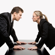 Caucasian mid-adult businessman and woman staring at each other with hostile expressions.